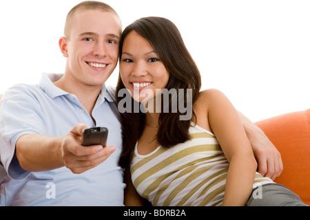 Junes Paar sitzt lachend auf dem Sofa und schaut fern - Stock Photo