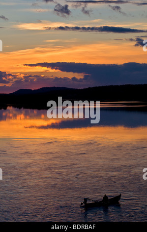 angler in boat on torne river at afterglow, lapland, sweden - Stock Photo