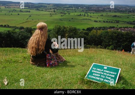View over fields from the top of Glastonbury Tor Somerset England with lady meditating on the lawns - Stock Photo