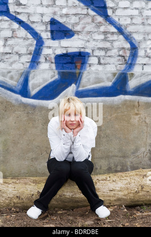 young sad woman in front of a graffiti - Stock Photo