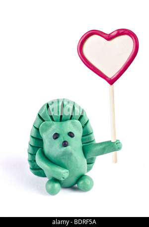 Plasticine hedgehog retaining heart-shaped banner - Stock Photo
