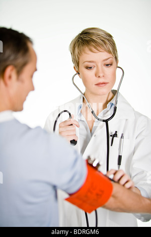 A female doctor using a blood-pressure gauge - Stock Photo