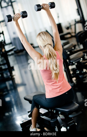 Woman weight training at a gym - Stock Photo