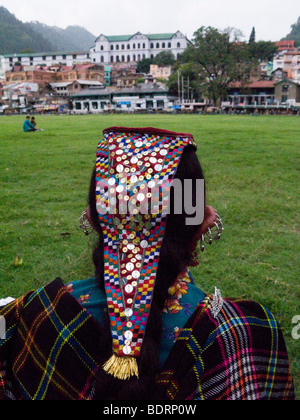 Indian woman with ethnic sequined headdress relaxing at the edge of the Chowgan (green space). Chamba, Himachal - Stock Photo