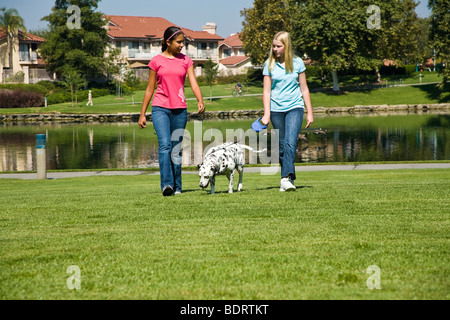 Front view two girls hang hanging out together Hispanic Caucasian teenage middle girls walk dalmatian talk child - Stock Photo