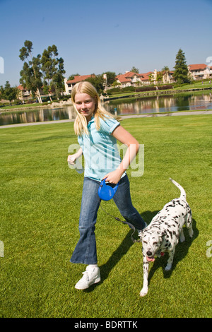 California Caucasian young girl 11-12 years old and dalmatian dog running in the park child playing play plays dog - Stock Photo