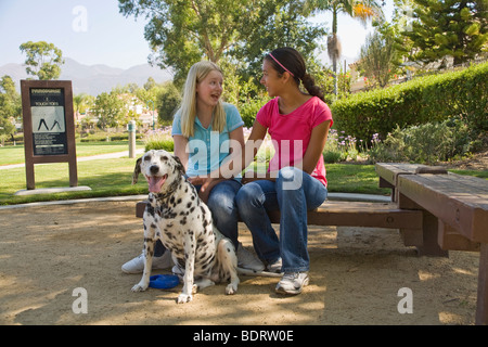 Hispanic and Caucasian diverse multi ethnic middle school Tween tweens  girls sitting and talking in park. Front - Stock Photo
