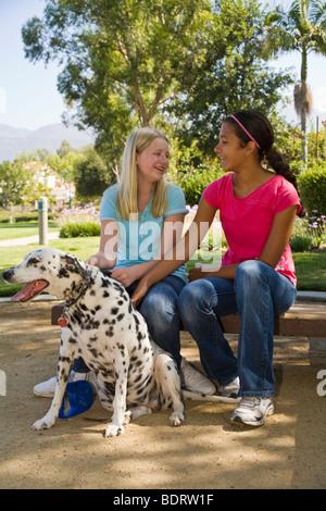 Hispanic and Caucasian junior Tween tweens girls sitting and talking in park. MR diverseTween tweens dog owner front - Stock Photo