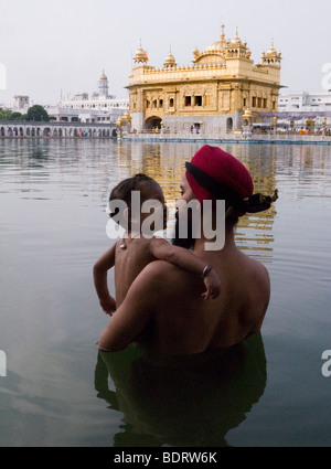 Sikh man and daughter in the waters – the Sarovar / water tank – around the Golden Temple (Sri Harmandir Sahib) - Stock Photo