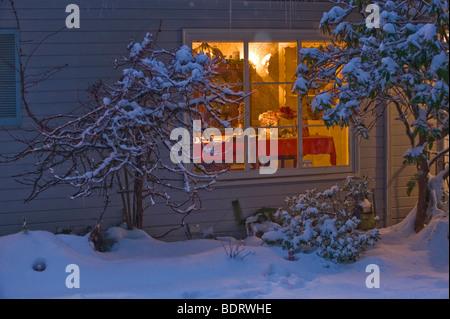 cozy home warm glow on snowy night - Stock Photo