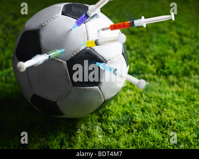 five syringes threaded in soccer ball. Copy space - Stock Photo