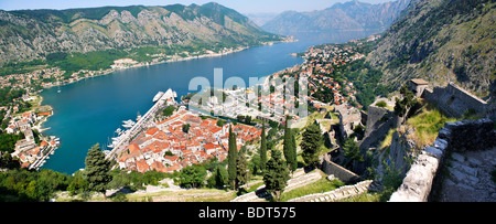 View from the medieval hill fortifications above Kotor across roof tops and Kotor Bay - Montenegro - Stock Photo