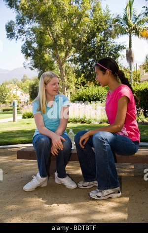 Two Racially mixed mix Ethnic diversity Tween tweens hanging out Multi ethnic Hispanic Caucasian teenage girls talking. - Stock Photo