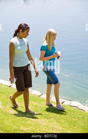 Hispanic and Caucasian Tween tweens age girls walk along edge of lake.  MR - Stock Photo