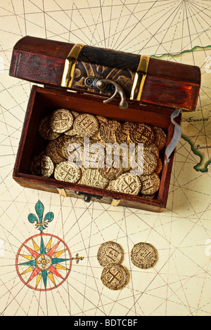 Open treasure chest box on old map with compass rose - Stock Photo