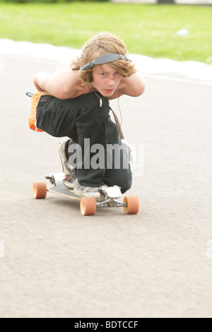 Closup of a young man with headphones crouched on a Skateboard during a charity marathon - Stock Photo