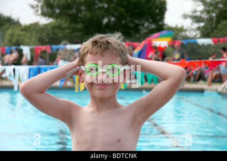 Young boy swimmer wearing green goggles at outdoor swimming meet - Stock Photo