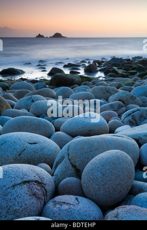 Circular boulders at Porth Nanven beach, with The Brisons island on the horizon, Cornwall, England. Spring (May) - Stock Photo