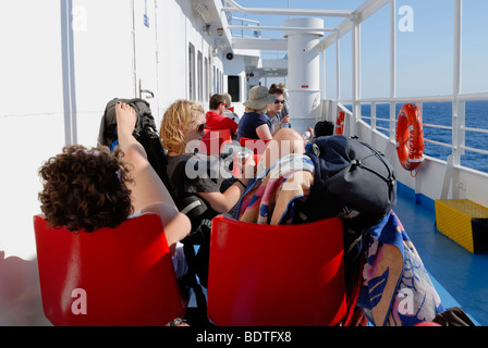 Tourists travel from Santori (Thira) Island to Ios Island on the ferry F/B Artemis at sunny summer morning. F/B - Stock Photo