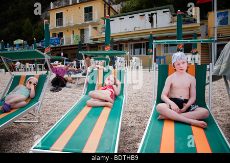 brother and two sisters on stripy beach loungers in italy - Stock Photo