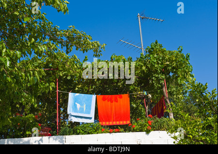 Towels hanging on washing line in village of Pastra on the Greek Mediterranean island of Kefalonia Greece GR - Stock Photo