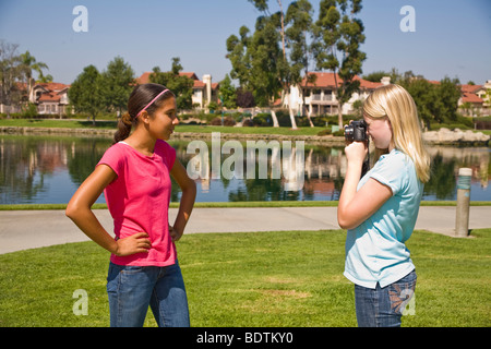 Caucasian junior high girl takes photo of her Hispanic friend.MR  © Myrleen Pearson