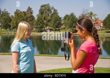 two girls 11-12 year old years hanging out Hispanic junior high girl takes photo Caucasian friend.young person people nature, natural surroundings Myrleen Pearson