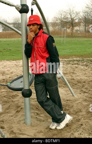 Teenage boy loitering at playground - Stock Photo