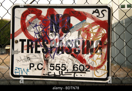 No Trespassing Sign With Graffiti Posted On Chain Link