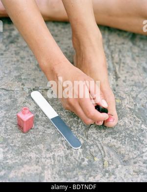 Woman using nail polish - Stock Photo