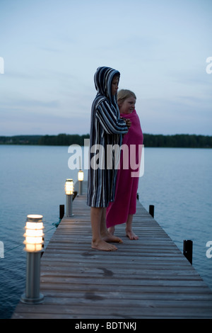 Two children wrapped in bathrobes on a jetty - Stock Photo