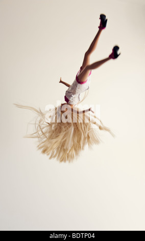 Barbie doll falling against a white background - Stock Photo