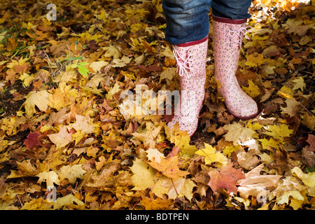 A woman wearing rubber boats in autumn forest - Stock Photo