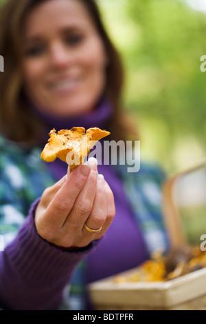 A woman holding a mushroom - Stock Photo