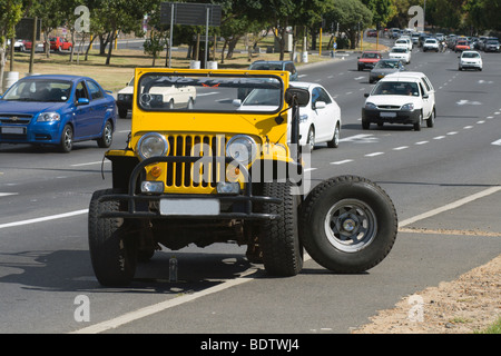 Yellow SUV with damaged rear wheel in Cape Town, South Africa - Stock Photo