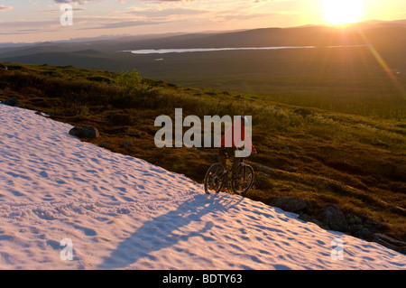 mountainbikerin am rande eines schneefeldes, gaellivare, lappland, schweden, downhill cyclist on a snow field, lapland, - Stock Photo
