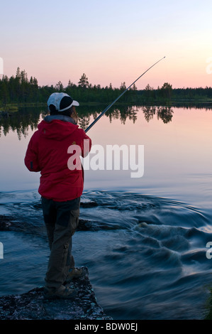 anglerin in abenddaemerung am see in lappland, schweden, female angler at sundwon at lake in swedish lapland - Stock Photo