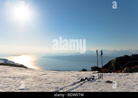 schier und stoecke im schnee, ofotfjorden, narvik, nordland, norwegen, skis in the snow at with view at fiord, norway - Stock Photo