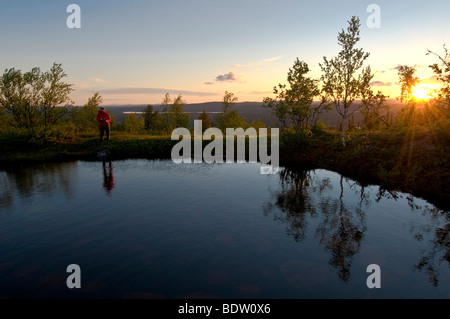 female angler at a mountain lake in lapland at midnight sun, sweden - Stock Photo