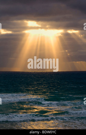Beams of light break through a dense bank of black clouds over the ocean, Mangawhai Head, Auckland, North Island, - Stock Photo