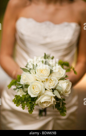 Bride holding wedding bouquet of white roses with short focus - Stock Photo