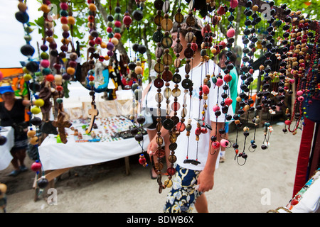 Tourists walk past a stall selling souvenirs beads in Manuel Antonio close to the entrance to the national park. - Stock Photo