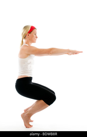 yoga awkward pose illustrated by attractive middle age fitness trainer teacher woman exercising and stretching - Stock Photo