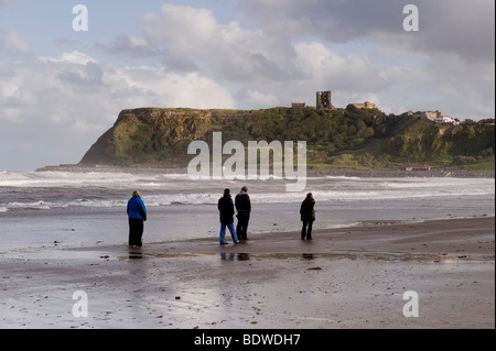 People walking on the beach, North Bay, Scarborough, towards the castle on the headland. - Stock Photo