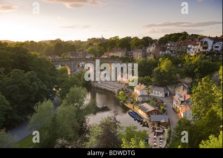 Scenic view at sunset over the sunlit viaduct, riverside buildings, houses & reflections on River Nidd - Knaresborough, - Stock Photo