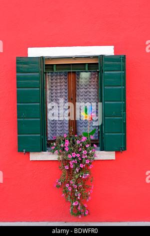 Brightly painted red house on Burano island in the Venice lagoon, Venice, Veneto, Italy, Europe - Stock Photo