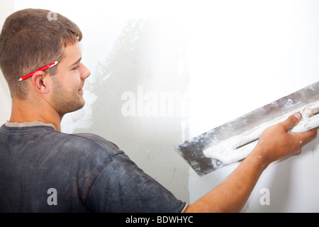 Man plastering the wall with a large spatula. At the corrosion imposed gypsum. Sharpness to face. Horizontal Directional - Stock Photo