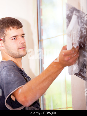 Man plastering the wall with a large spatula. At the corrosion imposed gypsum. Sharpness to face. Vertical Directional - Stock Photo