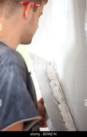 Man plastering the wall with a large spatula. At the corrosion imposed gypsum. Sharpness to spatula. Vertical Directional - Stock Photo