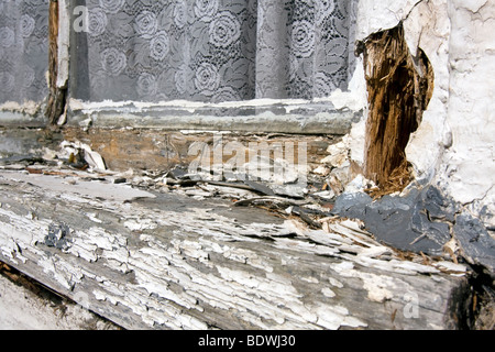 White paint peeling of an old, badly maintained, wooden windows frame. - Stock Photo